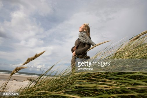 Germany, Schleswig Holstein, Amrum, Young woman on grassy sand dune