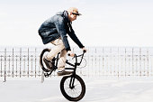 Germany, Schleswig Holstein, Teenage boy jumping with BMX bike
