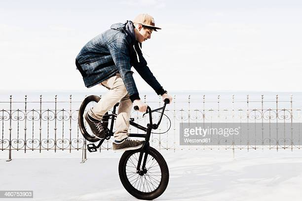 Germany, Schleswig Holstein, Teenage boy jumping with BMX bike