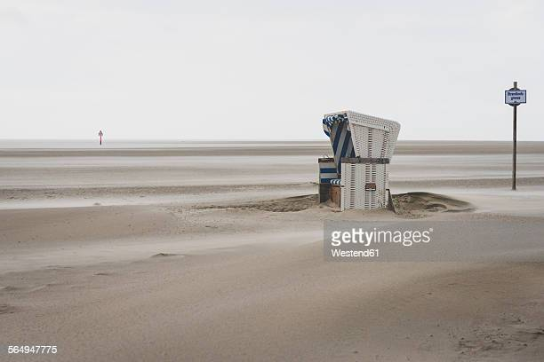 Germany, Schleswig-Holstein, St Peter-Ording, hooded beach chair in stormy weather