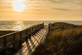 Germany, Schleswig-Holstein, Sylt, North Sea, wooden walkway through dune at sunset