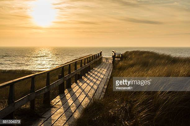 Germany, Schleswig-Holstein, Sylt, North Sea, wooden walkway through dune at sunset