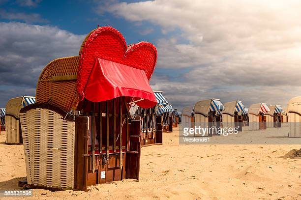 Germany, Schleswig-Holstein, Travemuende, hooded beach chair with red sunscreen