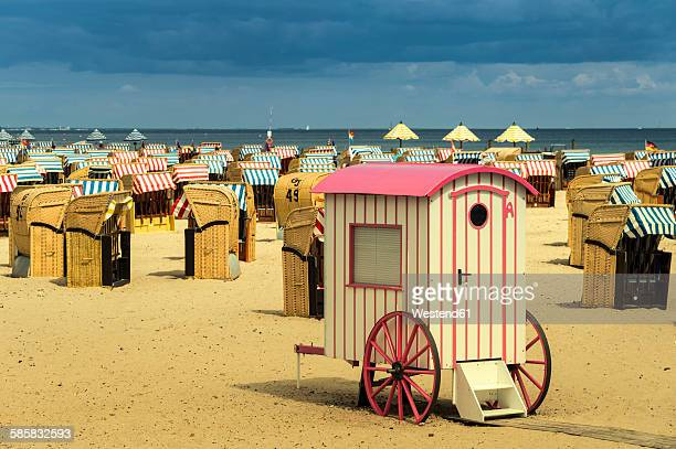 Germany, Schleswig-Holstein, Travemuende, roofed wicker beach chairs and changing cubicle