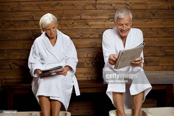 Germany, senior couple reading magazine in spa