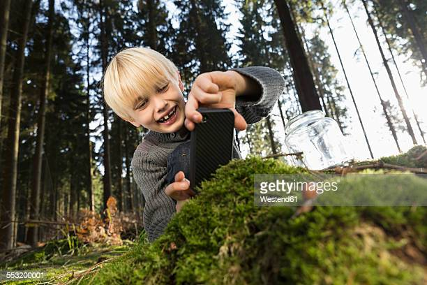 Germany, smiling little boy photographing nature in a forest