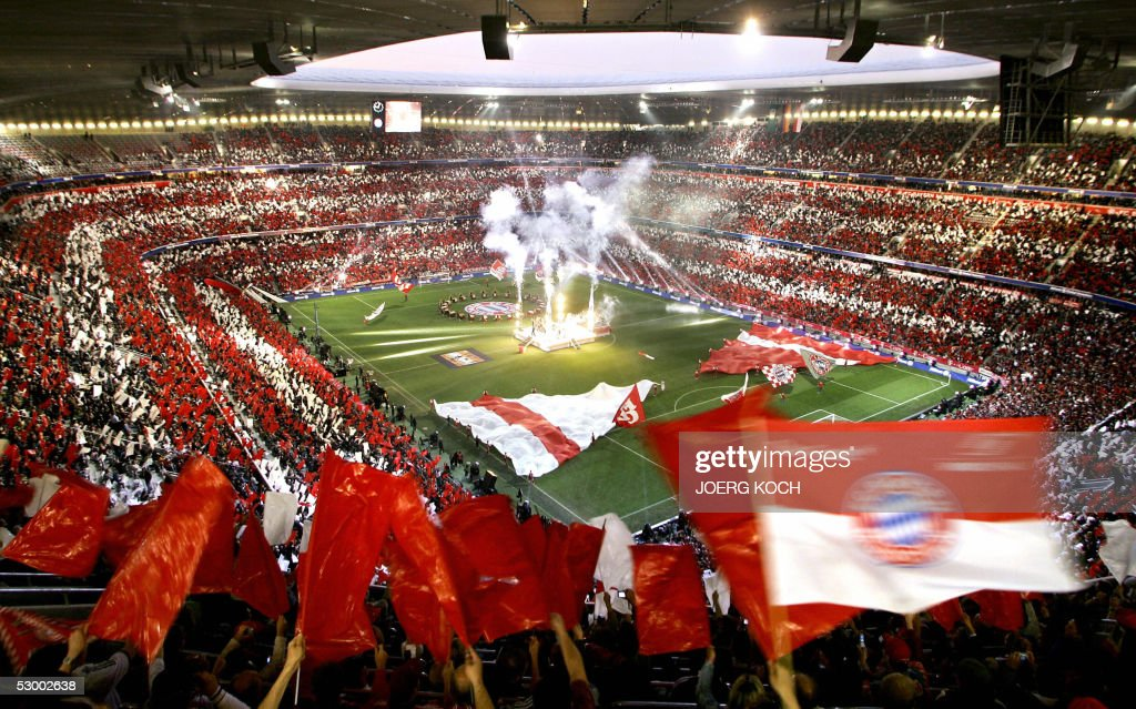 Spectators wave red and white flags the colours of Bayern Munich during the inauguration of the new Allianz Arena Football stadium 31 May 2005 in...
