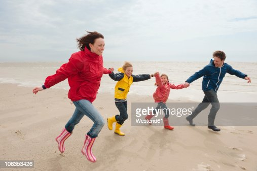 Germany, St. Peter-Ording, North Sea, Family holding hands and running on beach