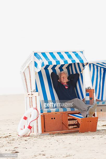 Germany, St. Peter-Ording, North Sea, Senior man relaxing on hooded beach chair