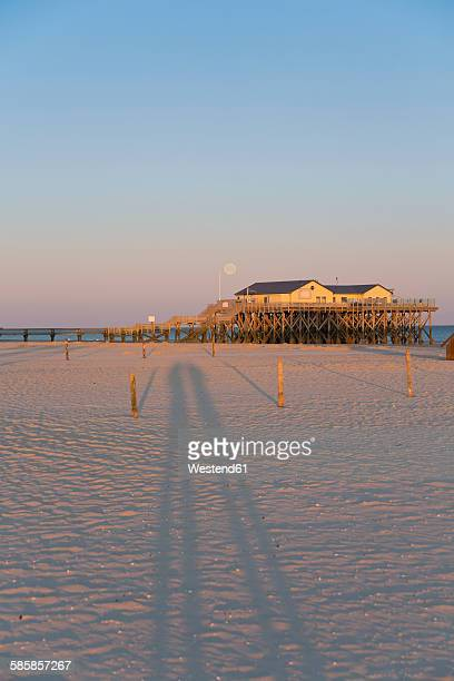 Germany, St Peter-Ording, pile dwelling on the beach by backlight
