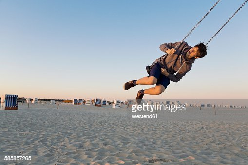 Germany, St Peter-Ording, teenager swinging on a swing at the beach