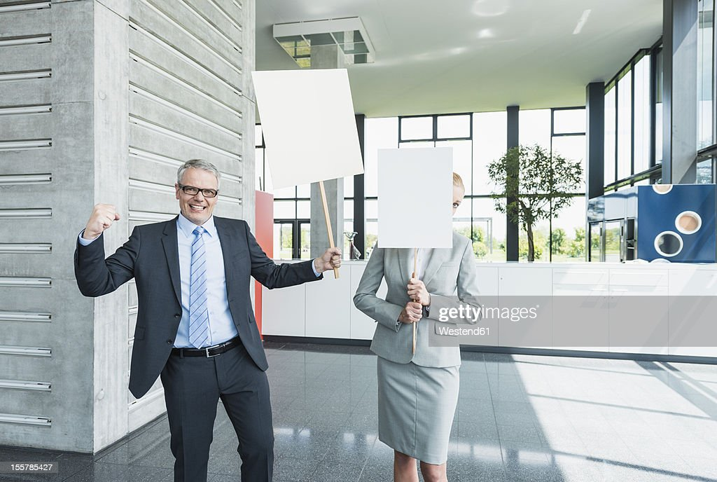 Germany, Stuttgart, Business people holding blank signs in office lobby, smiling : Stock Photo