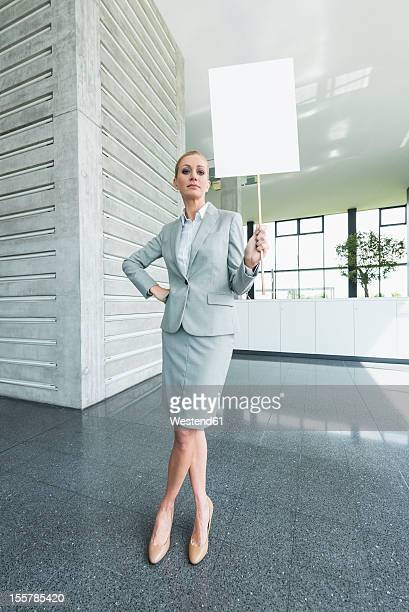 Germany, Stuttgart, Businesswoman standing with blank signs in office lobby, portrait