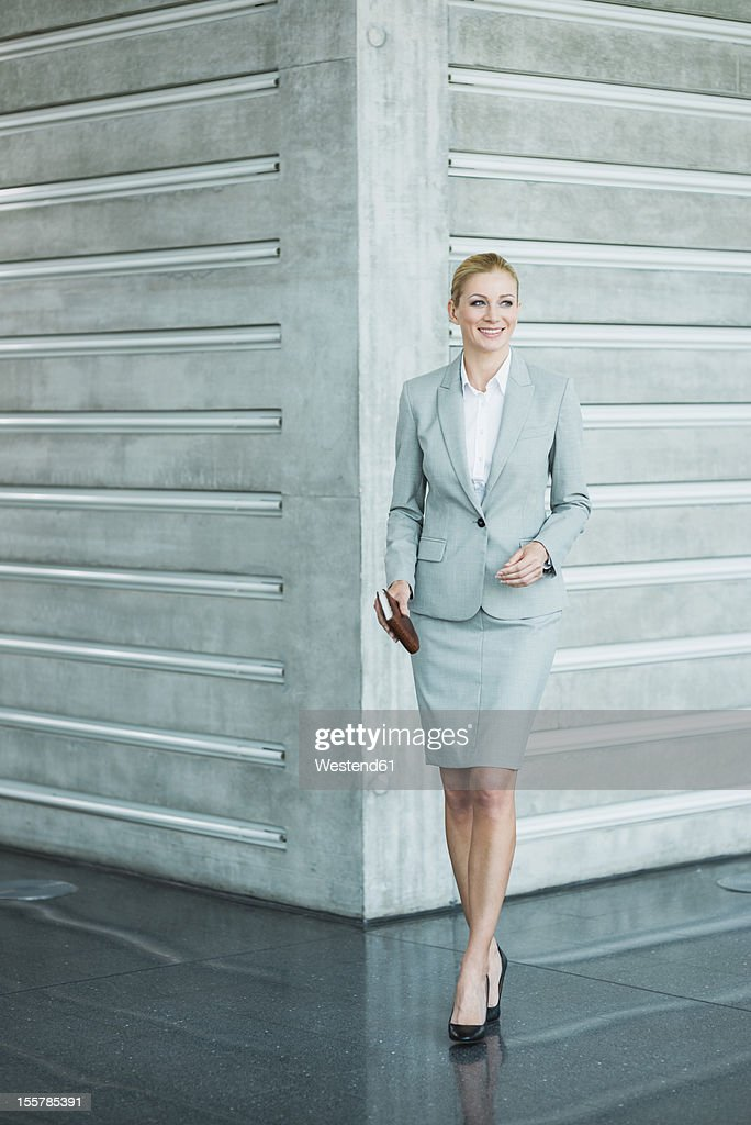 Germany, Stuttgart, Businesswoman standing with diary, smiling : Stock Photo