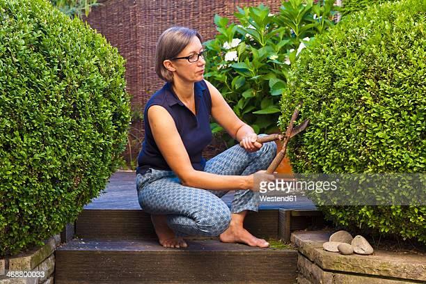 Germany, Stuttgart, Woman cutting box tree