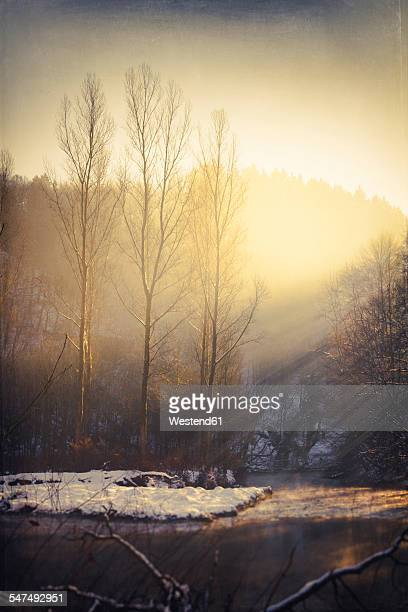 Germany, sunbeams over Wupper River at winter in the morning