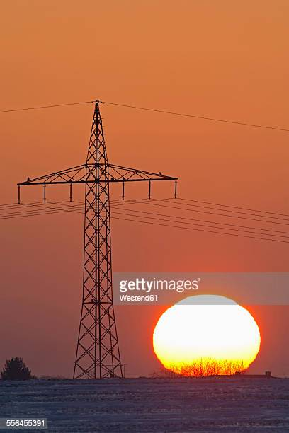 Germany, sunset besides electricity pylon