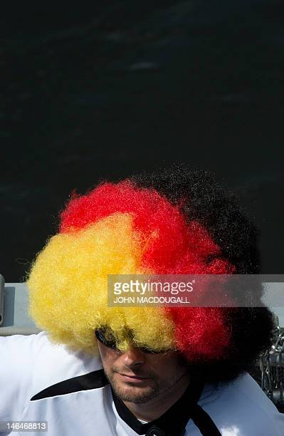 A Germany supporter wears an afro wig with the colours of the German flag as he sails down the river Spree in Berlin on a tourist ship June 17 2012...