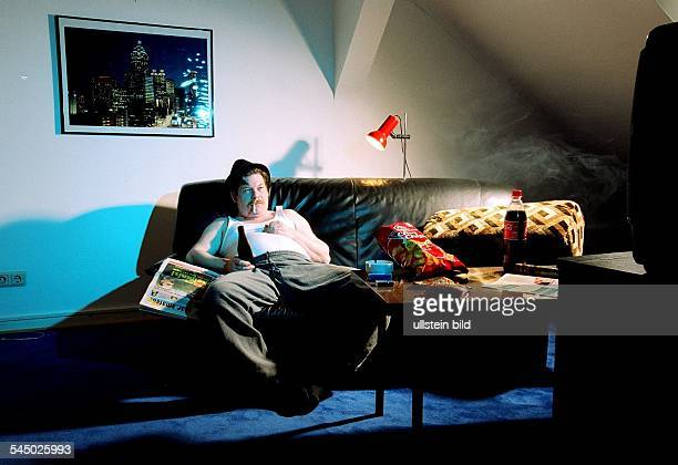 symbolic photo fat man with potato chips beer and cigarette is sitting on a sofa and is watching tv