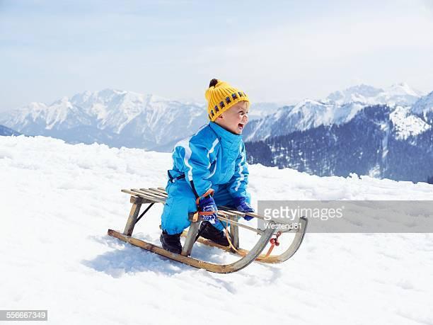 Germany, Tegernsee, Wallberg, smiling little boy sitting on sledge