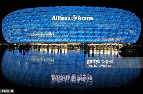 The illuminated new Allianz Arena Football stadium in Munich is reflected in the wet road 30 May 2005 after a friendly football match between TSV...