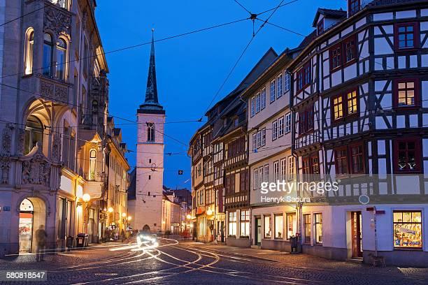 Germany, Thuringia, Erfurt, Illuminated city street and Allerheiligenkirche bell tower