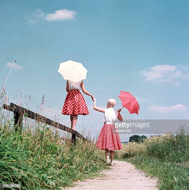two young women with sunshades walking