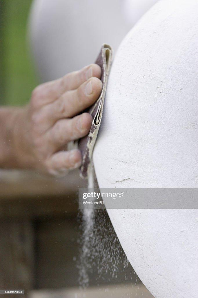 Germany, Upper Bavaria, Munich, Schaeftlarn, Sculptor polishing plaster