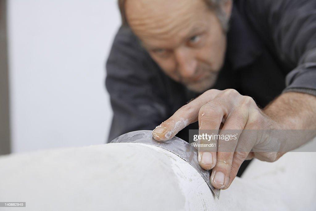 Germany, Upper Bavaria, Munich, Schaeftlarn, Sculptor working with gypsum