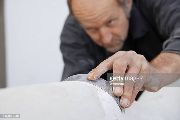 Germany, Upper Bavaria, Munich, Schaeftlarn, Sculptor working with gypsum