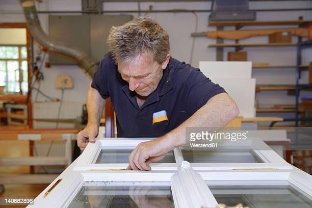 Germany, Upper Bavaria, Schaeftlarn, Carpenter preparing window