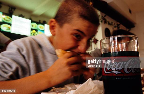 A young boy eating a doener kebab in a Turkish snackbar a Coca Cola to drink