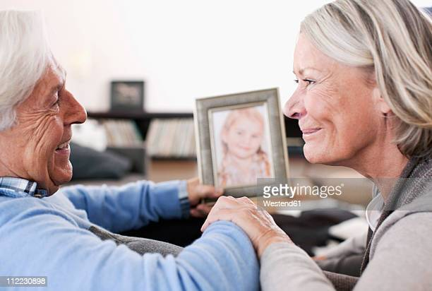 Germany, Wakendorf, Grandparents holding granddaughter photograph