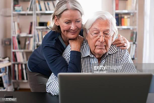 Germany, Wakendorf, Senior couple using laptop