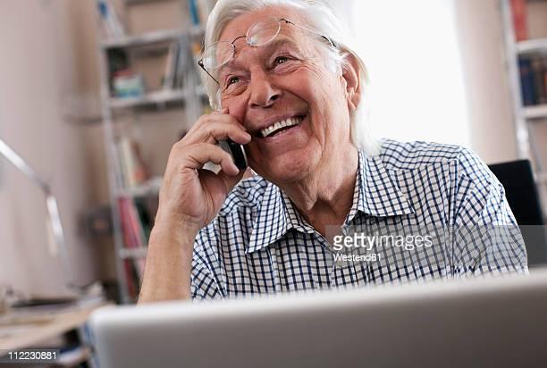 Germany, Wakendorf, Senior man on the phone with laptop, smiling