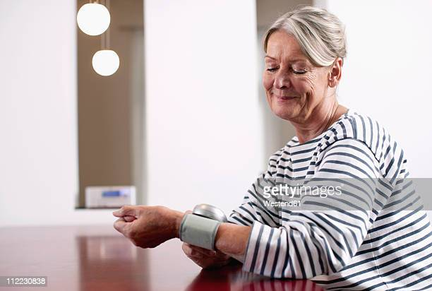 Germany, Wakendorf, Senior woman checking blood pressure