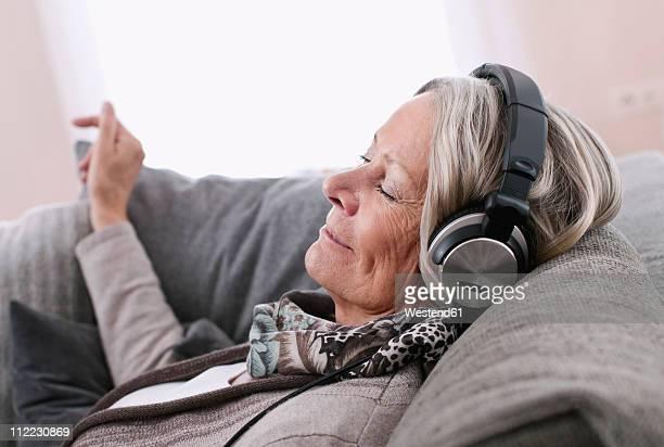 Germany, Wakendorf, Senior woman listening music