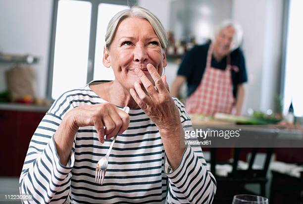 Germany, Wakendorf, Senior woman tasting noodles, man cooking in background