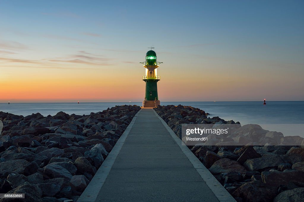 Germany, Warnemuende, view to lighthouse at dusk in front of the Baltic Sea