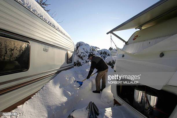 Winter camper Juergen Dietrich removes the snow from the way leading to his caravan 09 January 2006 in the eastern town of Altenberg Ore Mountains...