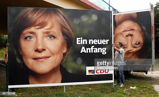 Workers dismantle an election poster featuring Angela Merkel leader of the Christian Democratic Union party and candidate for chancellor of the...