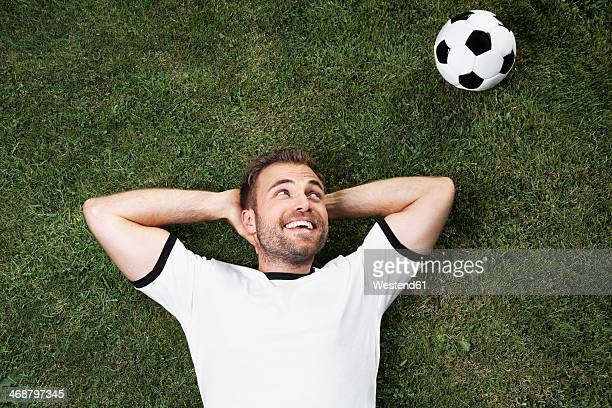Germany, Young man lying on lawn looking at football