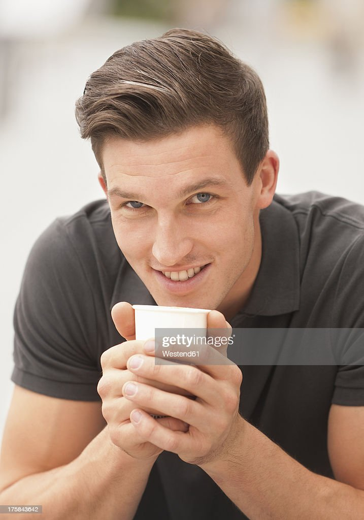 Germany, Young man with coffee cup, smiling, portrait : Stock Photo
