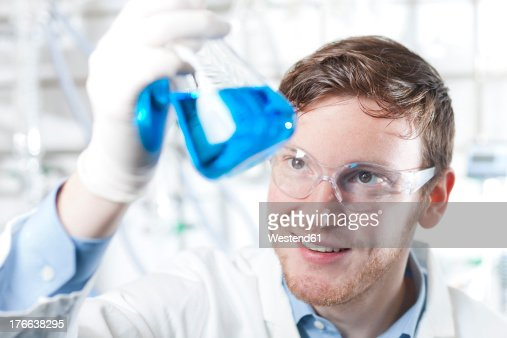 Germany, Young scientist checking blue liquid in erlenmeyer flask : Stock Photo
