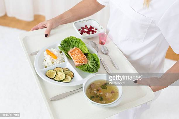 Germany, Young woman holding patient tray with main meal, close up