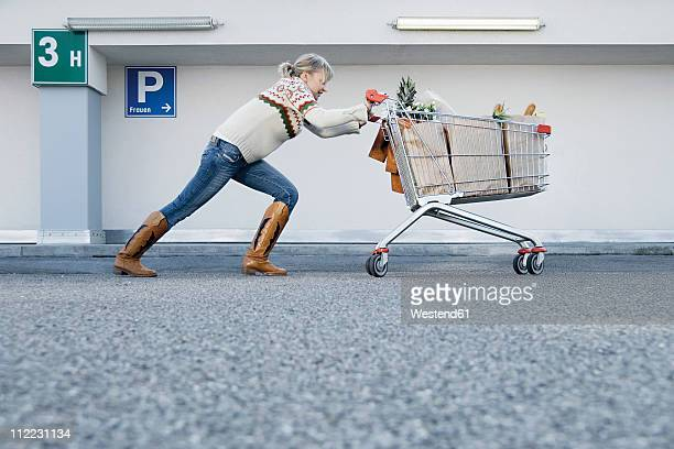 Germany, Young woman pushing shopping cart