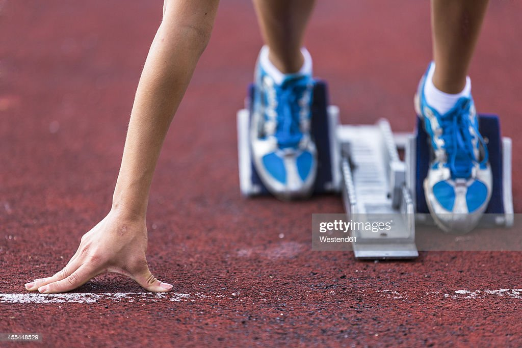 Germany, Young woman running from sprint start