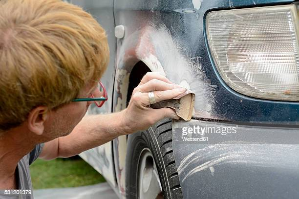 Germany, Zeuthen, Man mending car paint