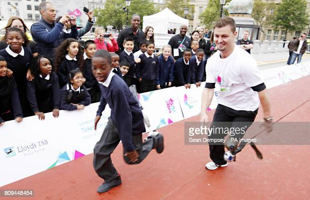 Germany's 100m runner Heinrich Popo races with Deese Madia age ten from the Curwen Primary school in London during the International Paralympic Day...