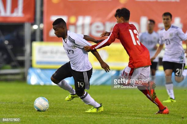Germany's 12yearold Youssoufa Moukoko and Austria's Simon Nosa Nelson viefor the ball during the friendly U16 football match between Austria and...